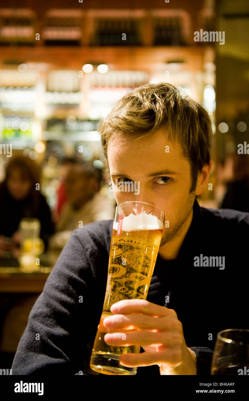A young man drinking in a bar - Stock Image