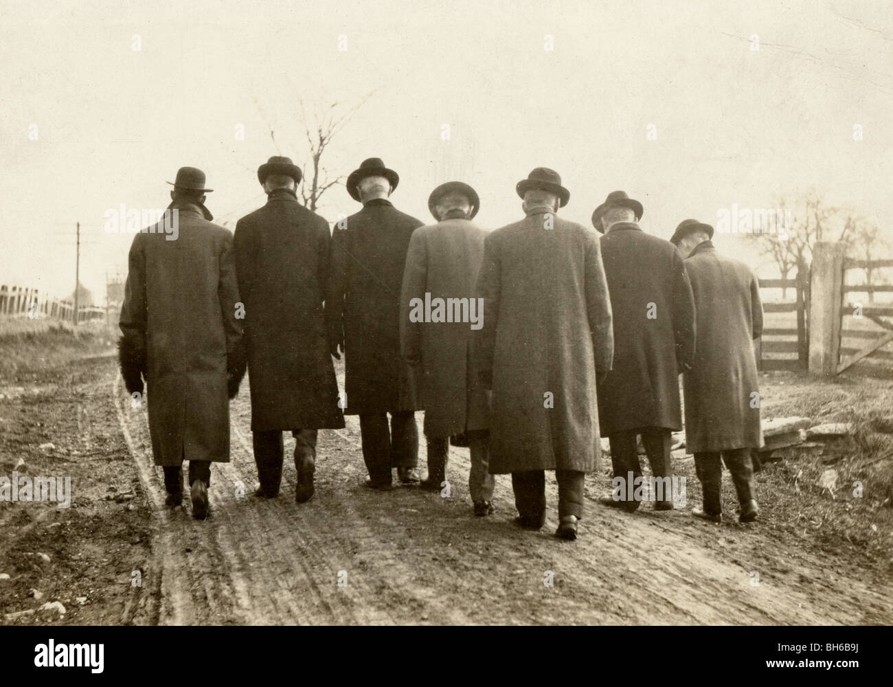 Seven Dispirited Men Trudging Along Country Road - Stock Image