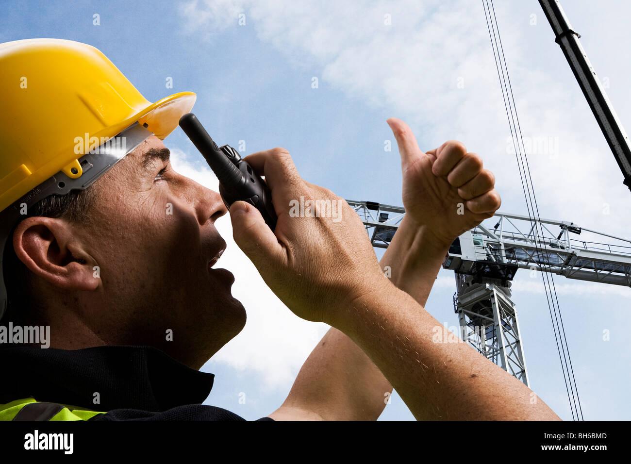 Construction worker directing crane - Stock Image
