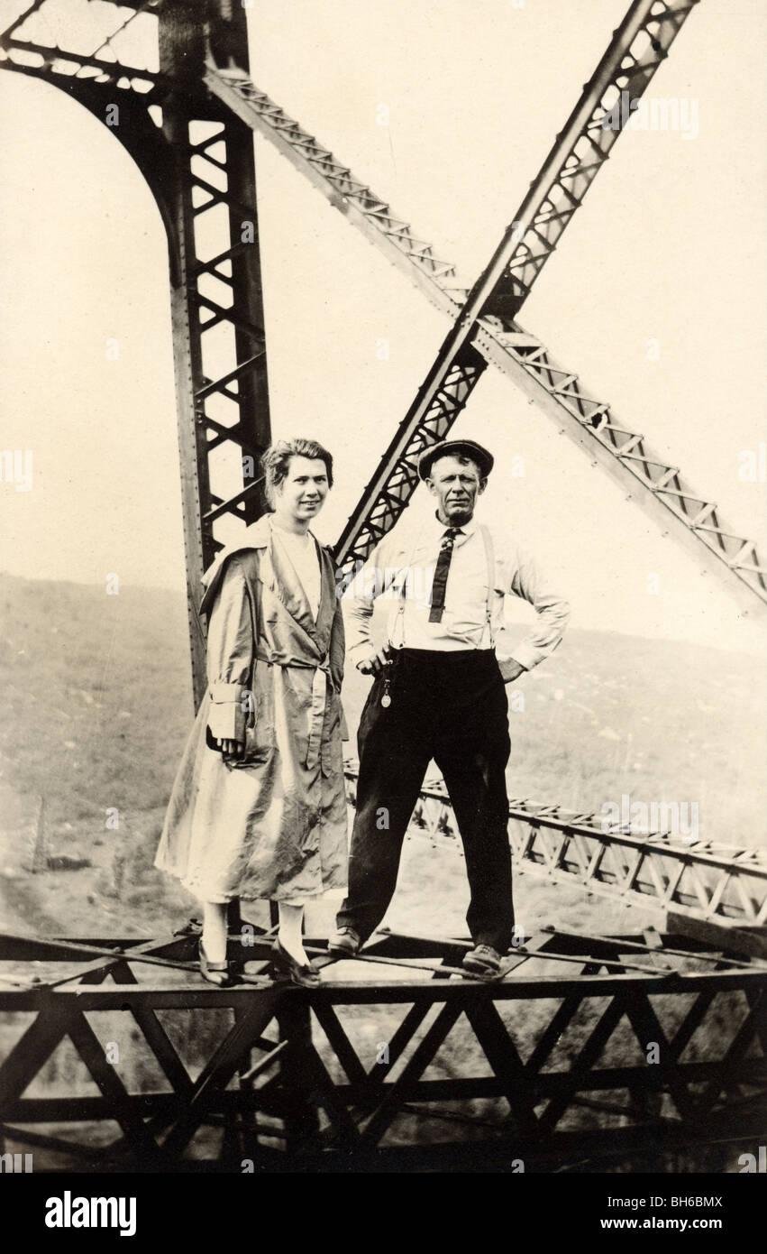 Daredevil Couple Standing on Bridge Pier - Stock Image