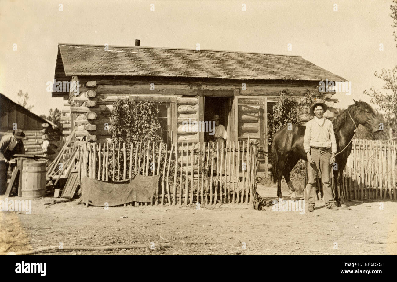 Cowboy & Wife at Log Cabin Homestead - Stock Image