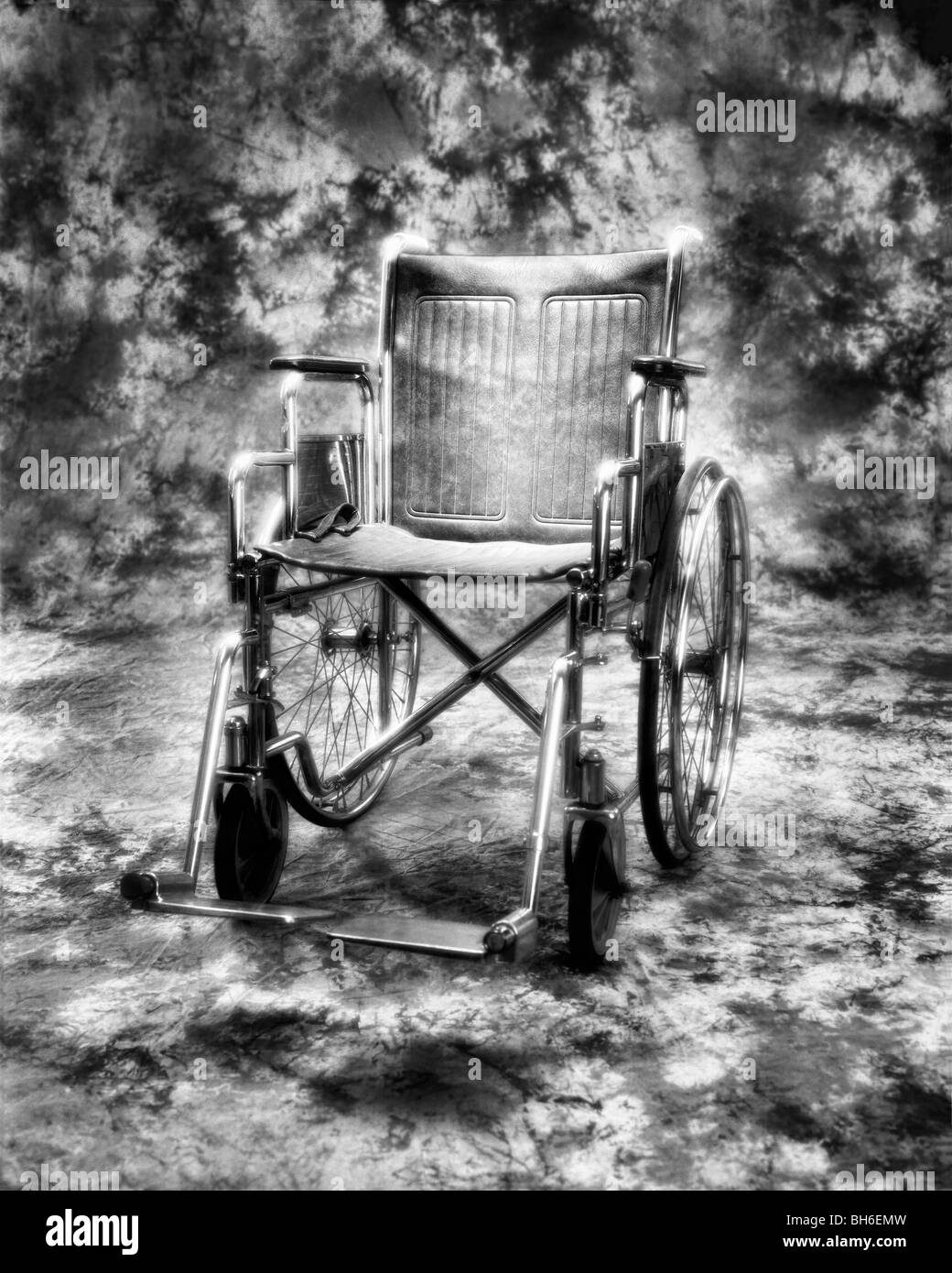 A dramatic and eerie shot of an empty wheelchair, this was shot on infrared black and white film - Stock Image