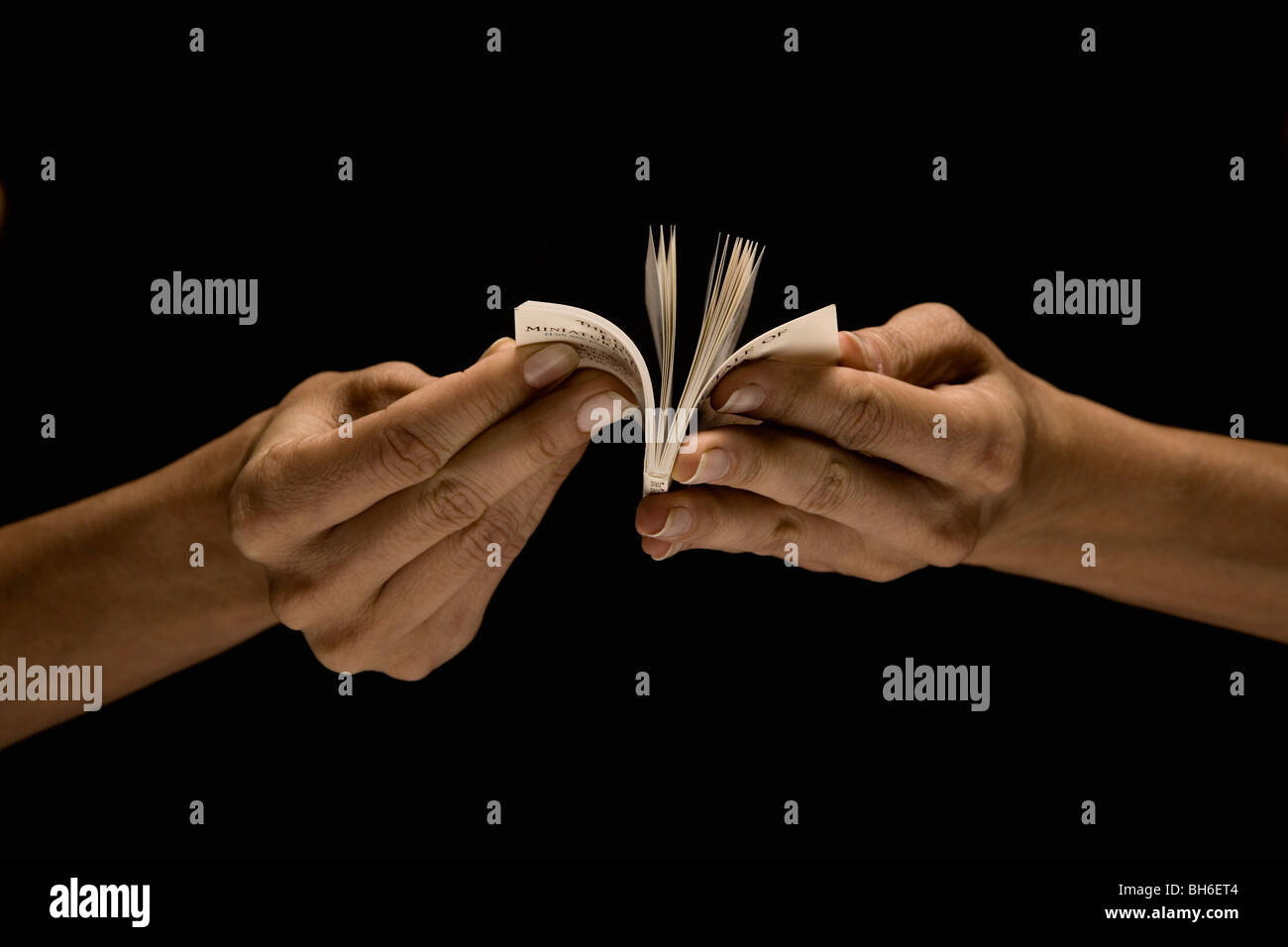 Hands reading tiny book - Stock Image