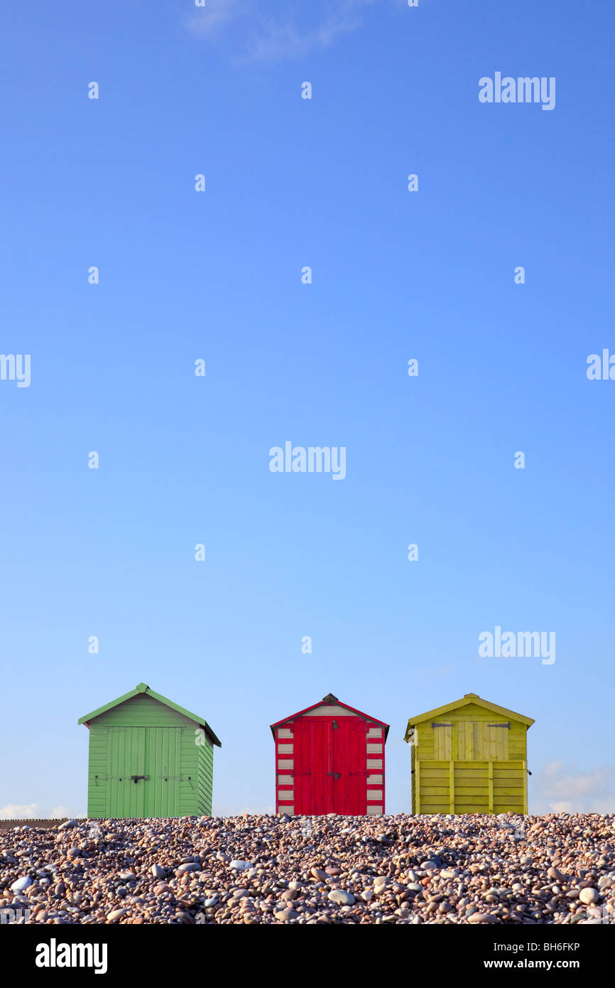 Three colourful beach huts against a bright blue sky, framed to allow copy space in the upper part of the image. - Stock Image