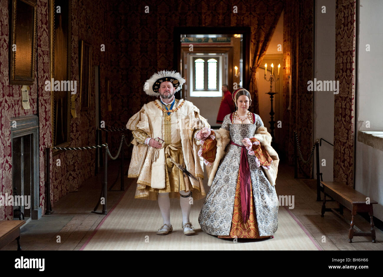 Two actors in Henry VIII and Ann Boleyn costumes walk along the haunted gallery in the State Apartments at Hampton - Stock Image