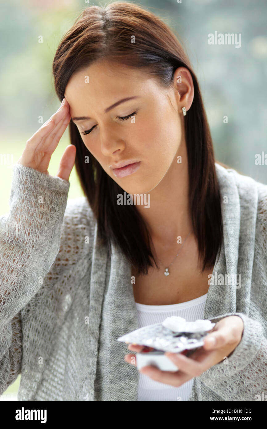 Woman with head ache tablets - Stock Image