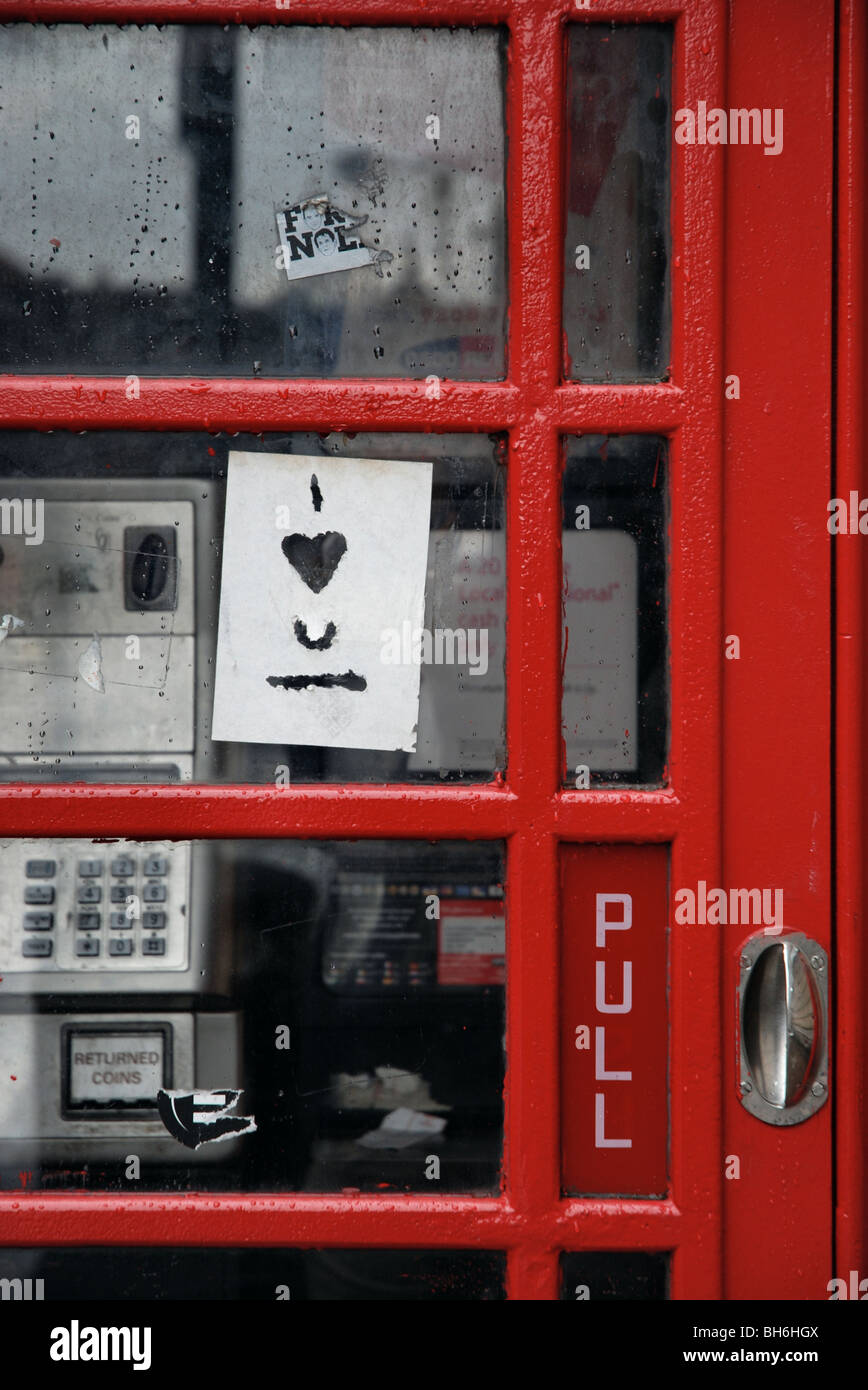 I heart U paper graffiti on a red telephone box - Stock Image