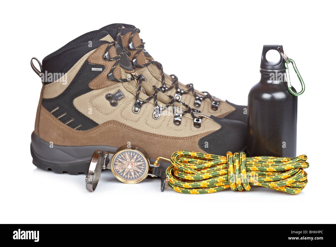 Hiking boots, canteen, rope and compass reflected on white background. Shallow depth of field - Stock Image