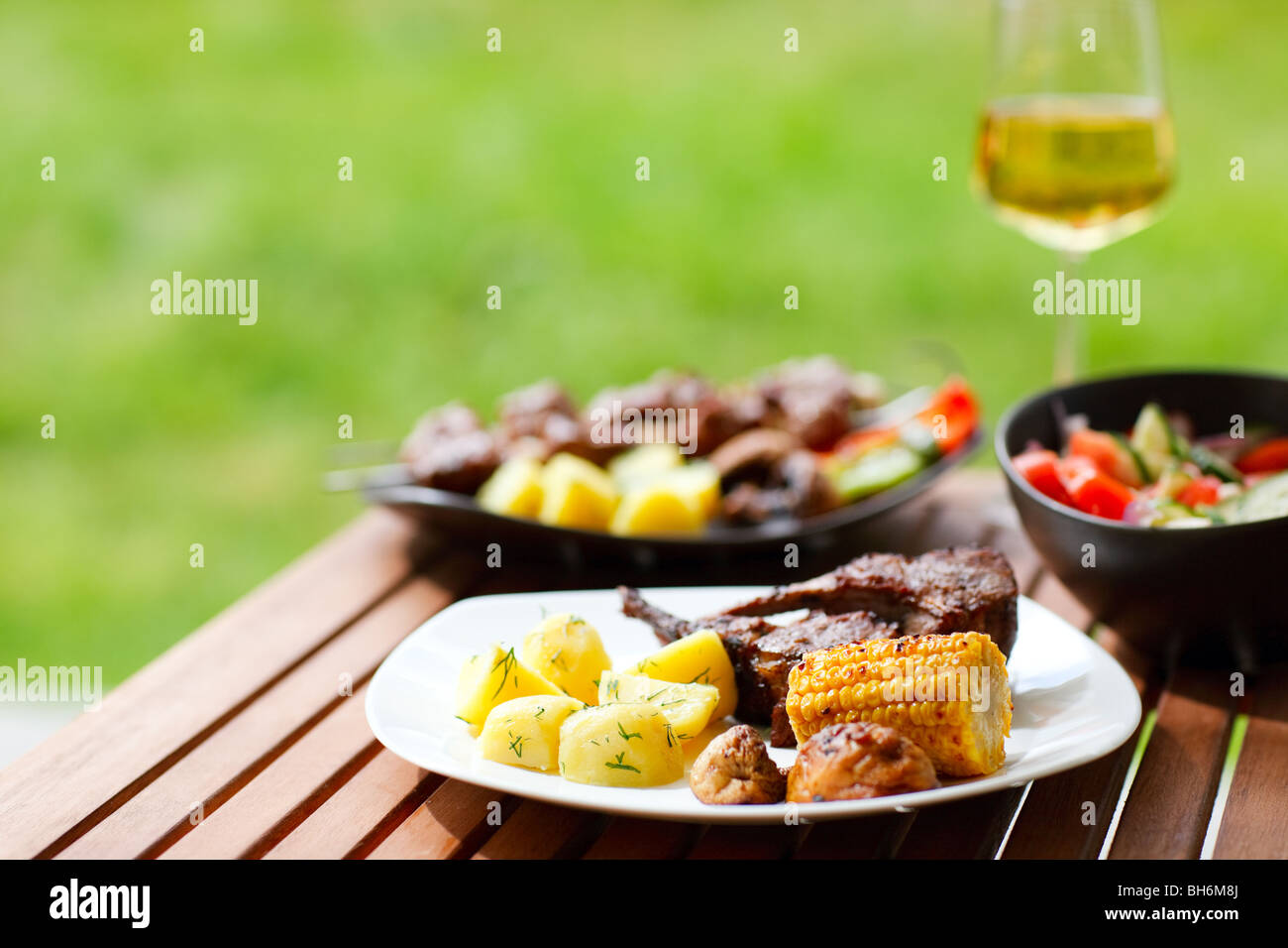 Grilling at summer weekend. Fresh grilled meat and vegetables served outdoors. - Stock Image