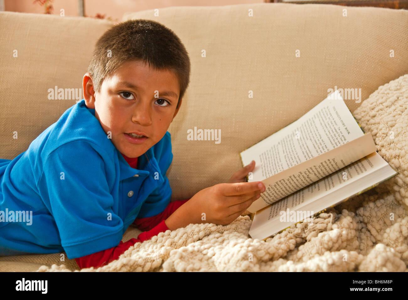 Hispanic 8-9 year old boy reading a book on sofa . United States, eye contact, rainy day activity POV MR United - Stock Image