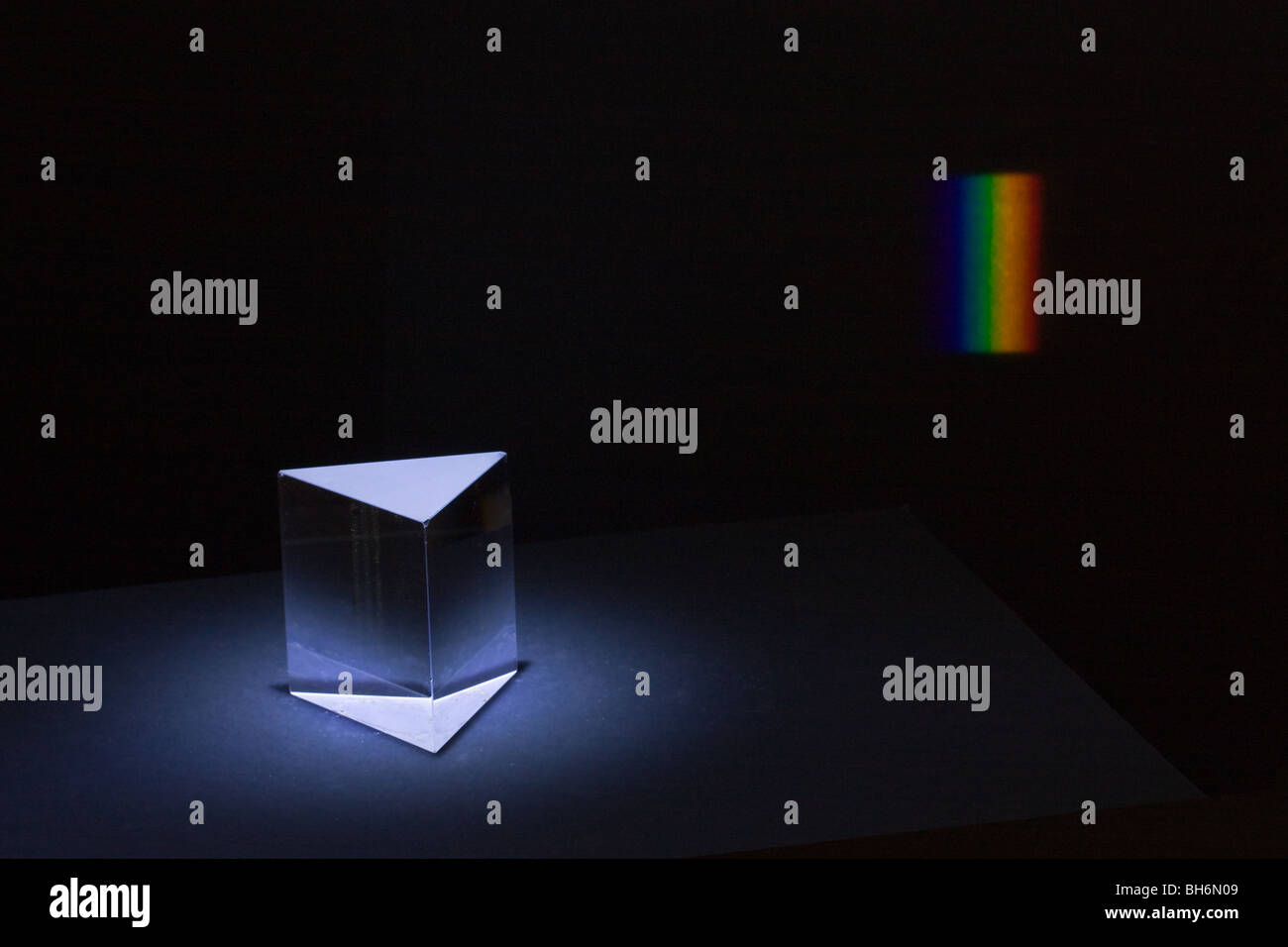 A glass prism and the spectrum it is dispersing - Stock Image