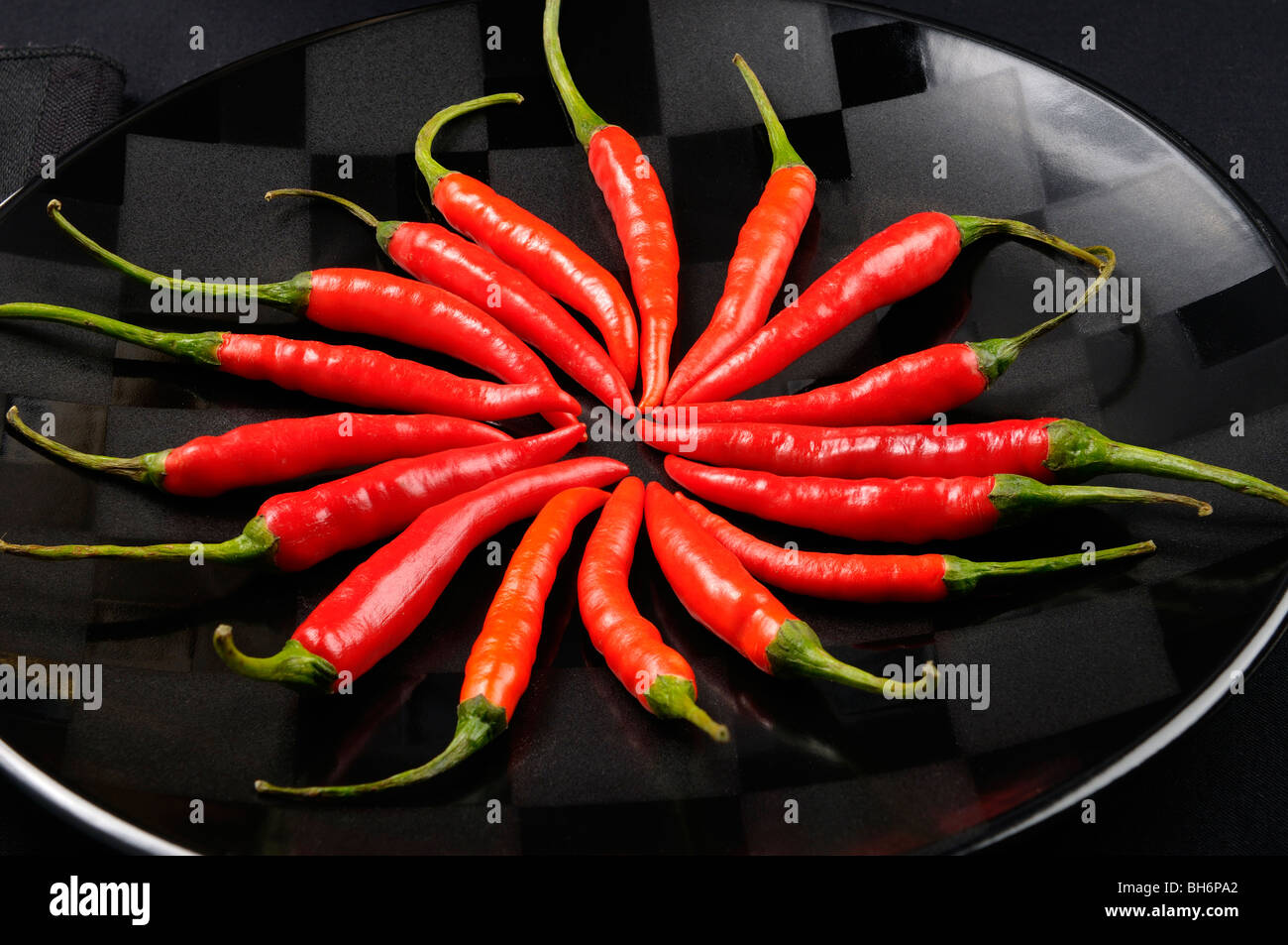 Close up of a ring of red hot Chili Peppers on a black plate - Stock Image