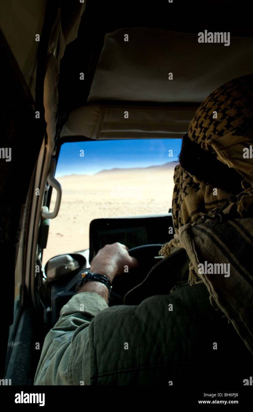 An Egyptian desert safari guide drives an off-road 4x4 land cruiser jeep route through the Gilf Kebir region of - Stock Image