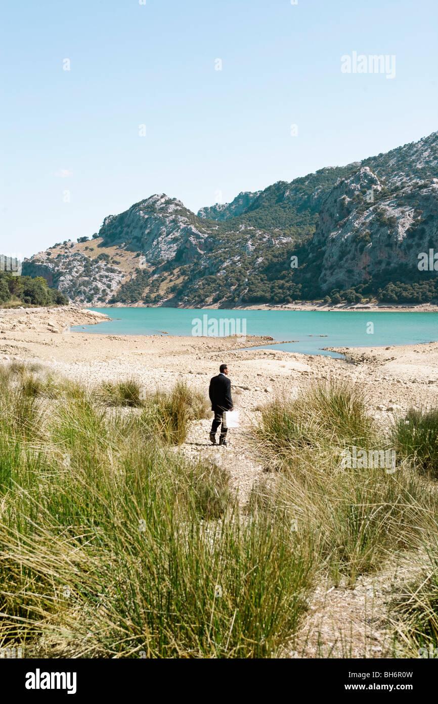 Business man walking by a lake - Stock Image