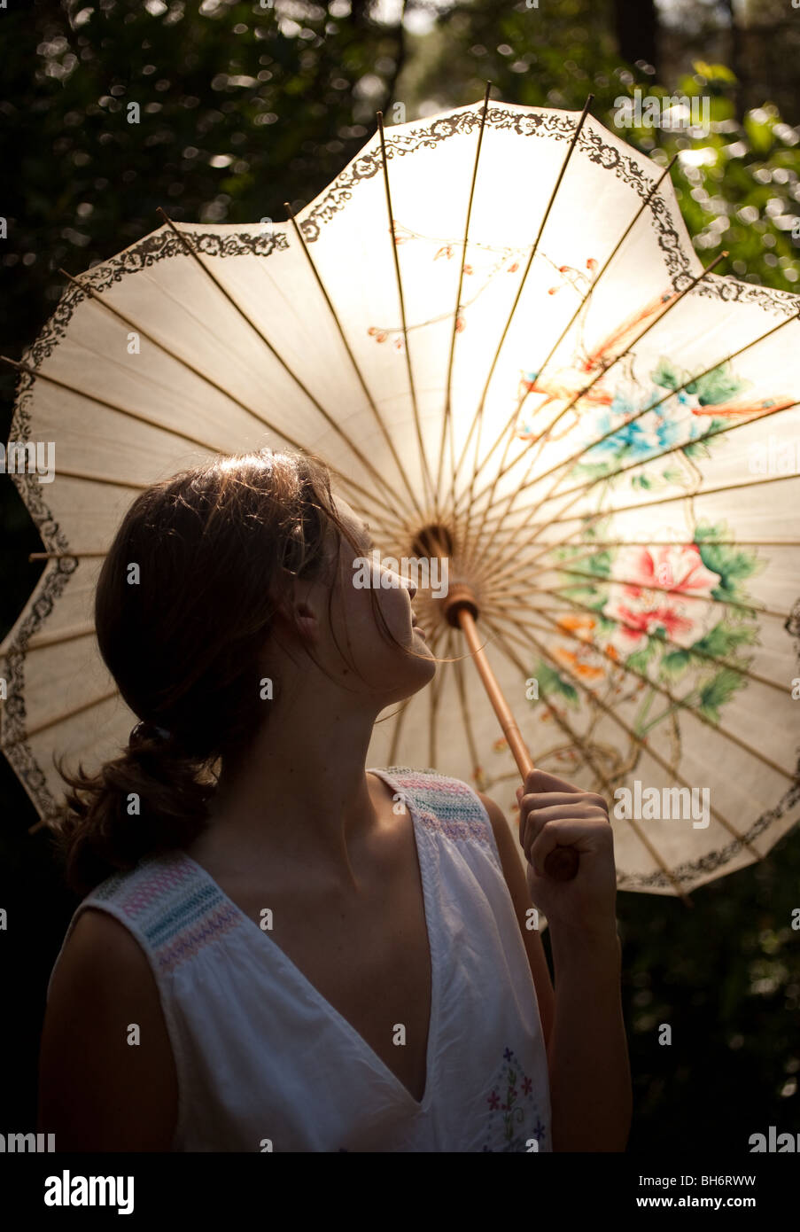 A teenage girl stands in her garden underneath her Chinese umbrella. - Stock Image