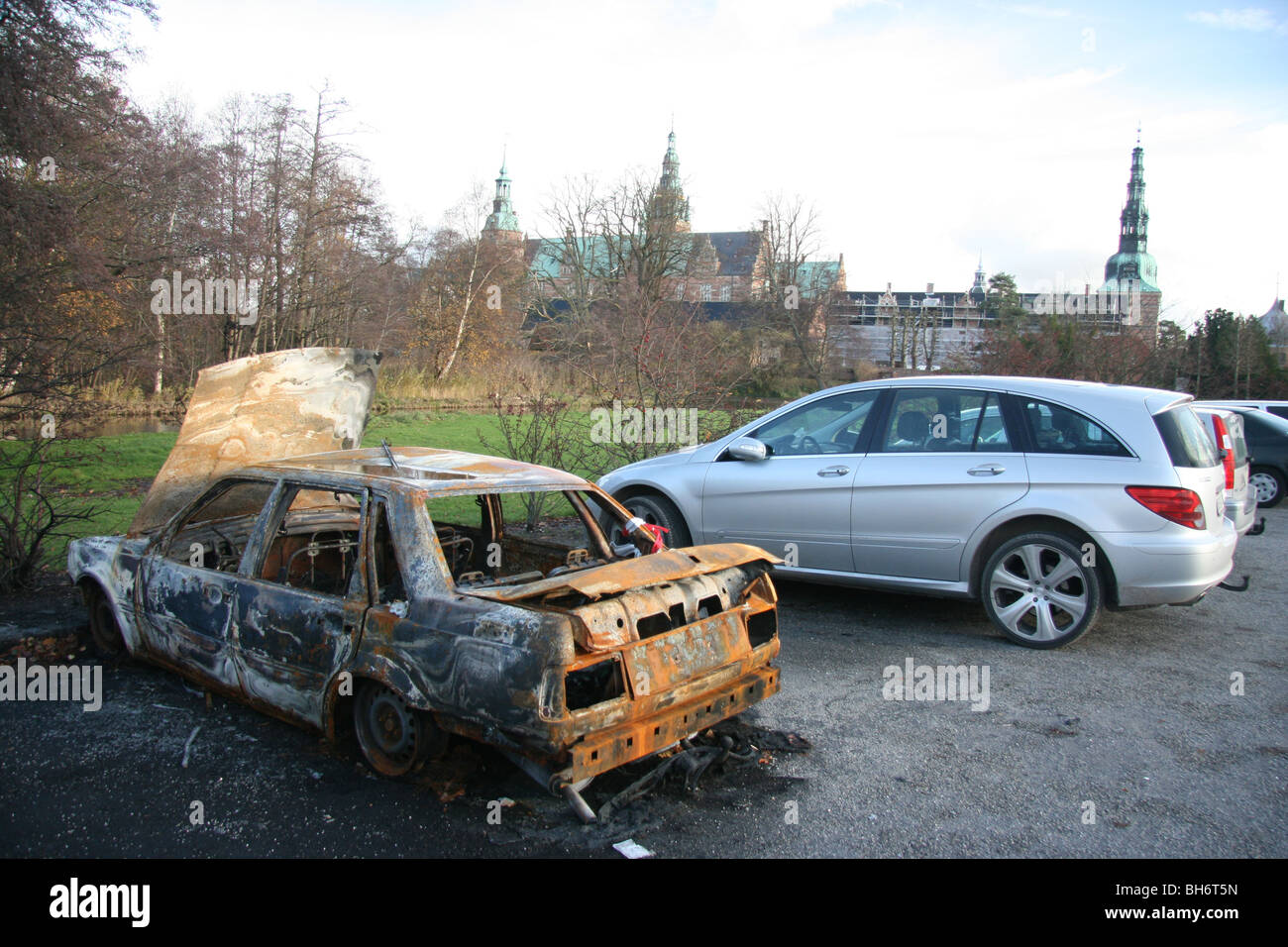 A burnt out car contrasting with new model cars and the castle in the parking lot of Frederiksborg Castle, Hilleroed, - Stock Image