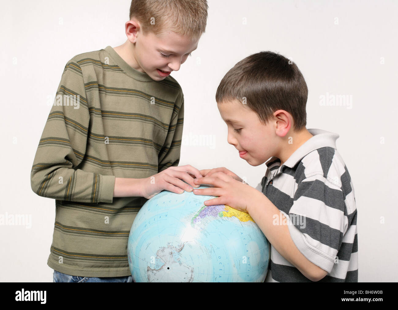 two elementary school age boys looking closely at a world globe on white background - Stock Image