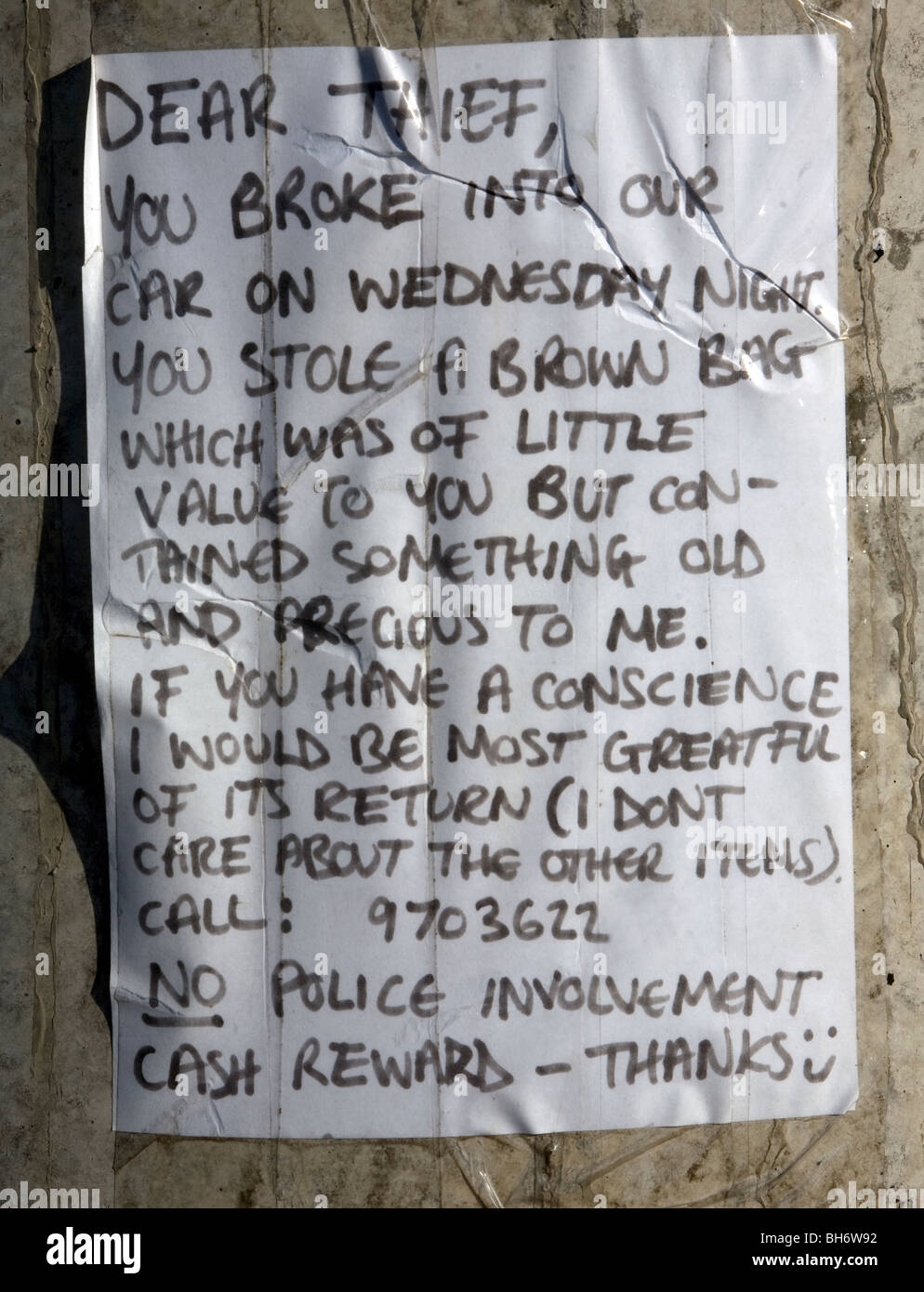 Letter written to thief posted on wall asking for return of property of sentimental value - Stock Image