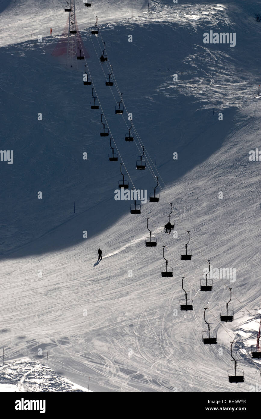 Ski lift going up mountain with only one skier visible and one skiing below on piste - Stock Image