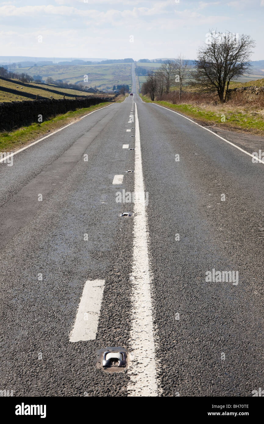 Long straight quiet country road in Northumberland National Park. Northumberland England UK Britain. - Stock Image