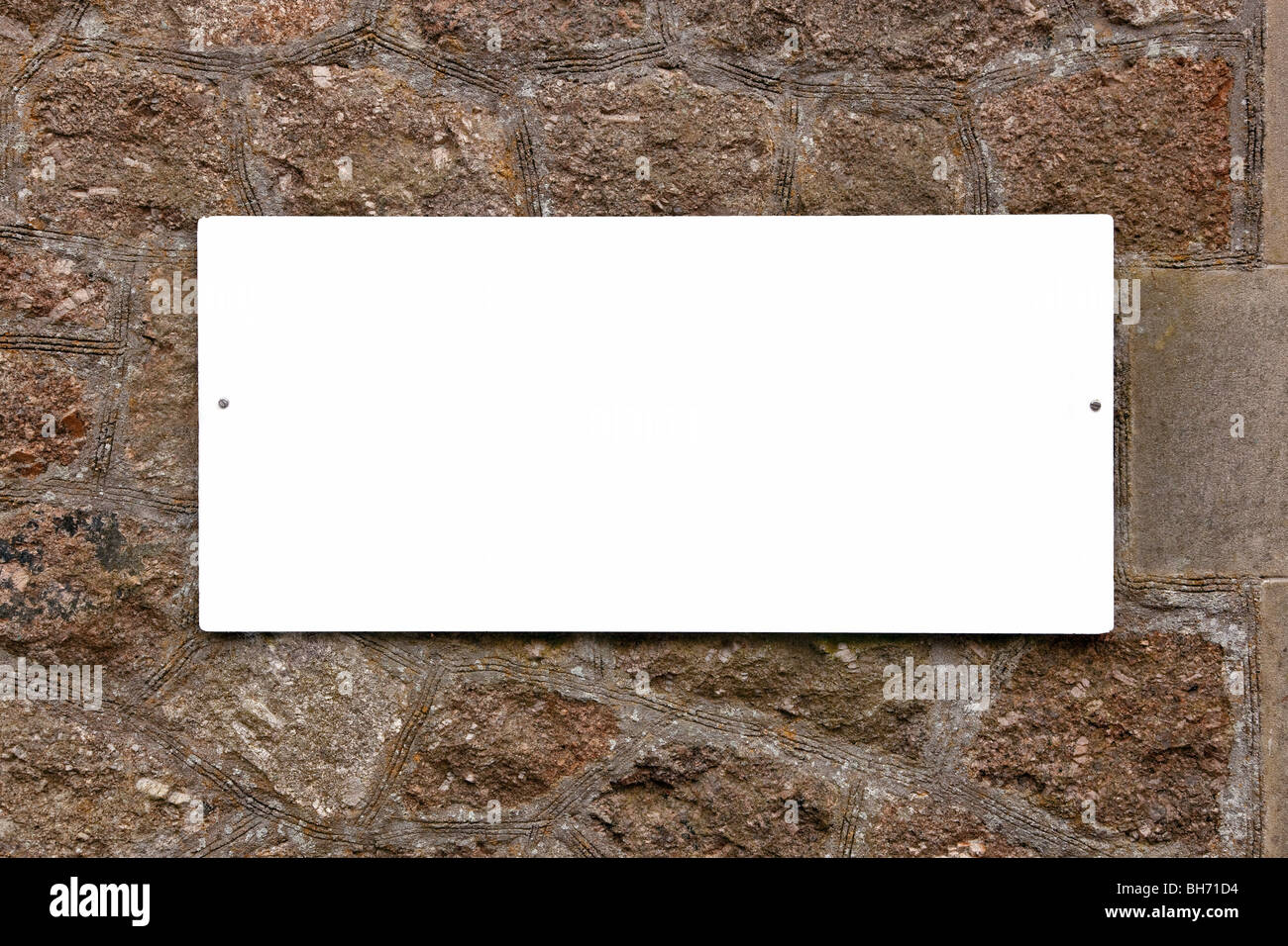 Blank white sign on an old stone wall, add your own message. - Stock Image