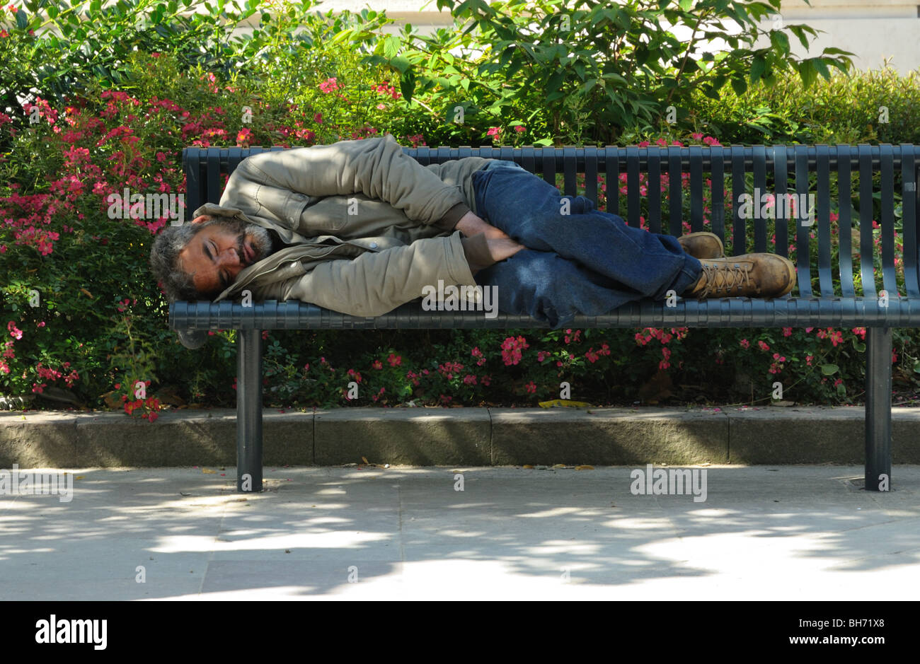 A homeless man sleeping on a public bench in a city park - Stock Image