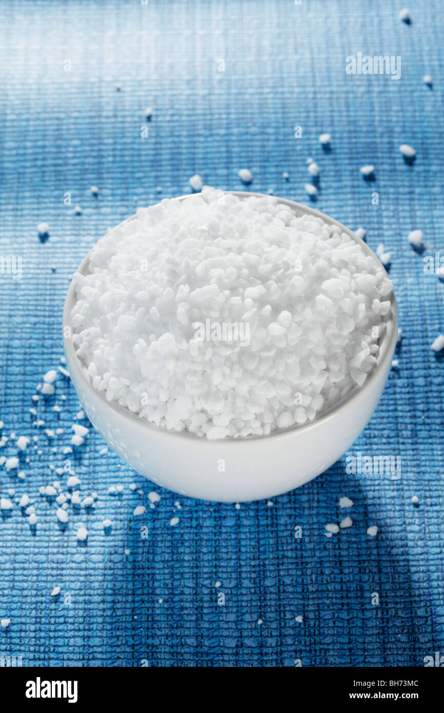 Coarse grained salt used in pepper mills and grinders in a small bowl - Stock Image