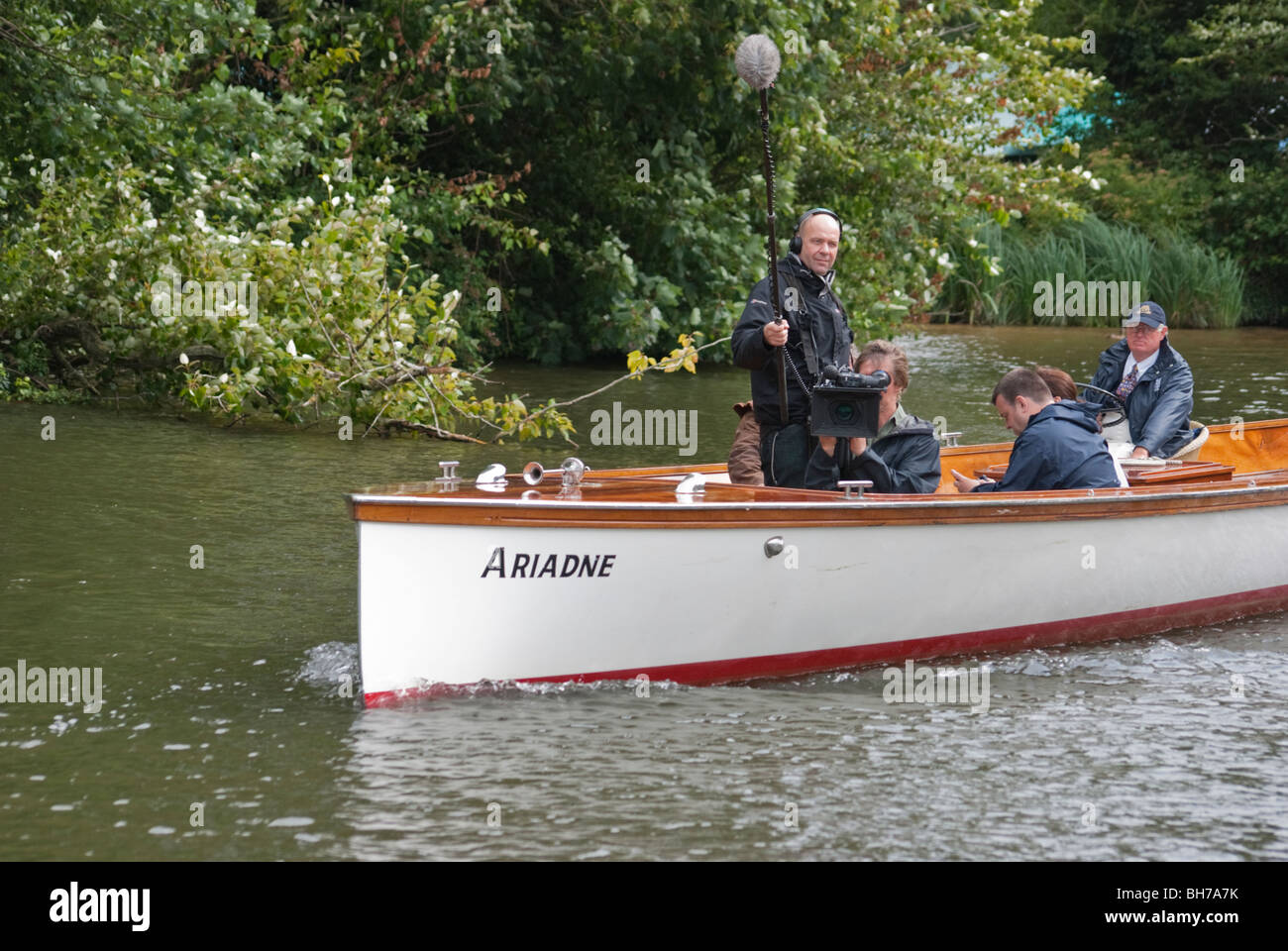 Television Camera Crew filming from a moving boat on the River Thames in Oxfordshire during the annual Swan Upping. - Stock Image