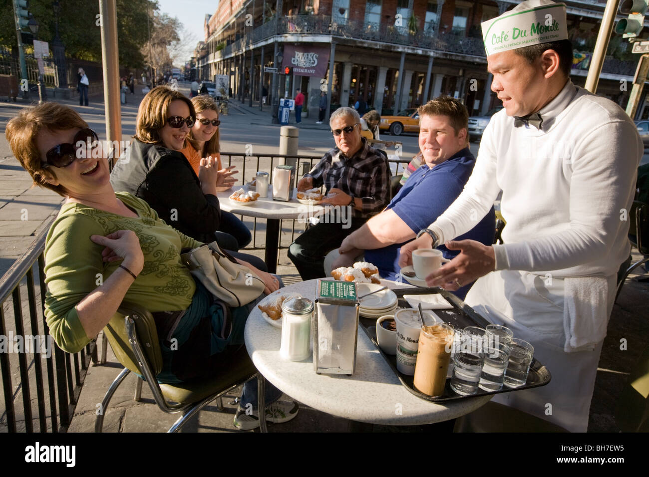 Waiter serving beignets and coffee at Cafe du Monde New Orleans, Louisiana - Stock Image