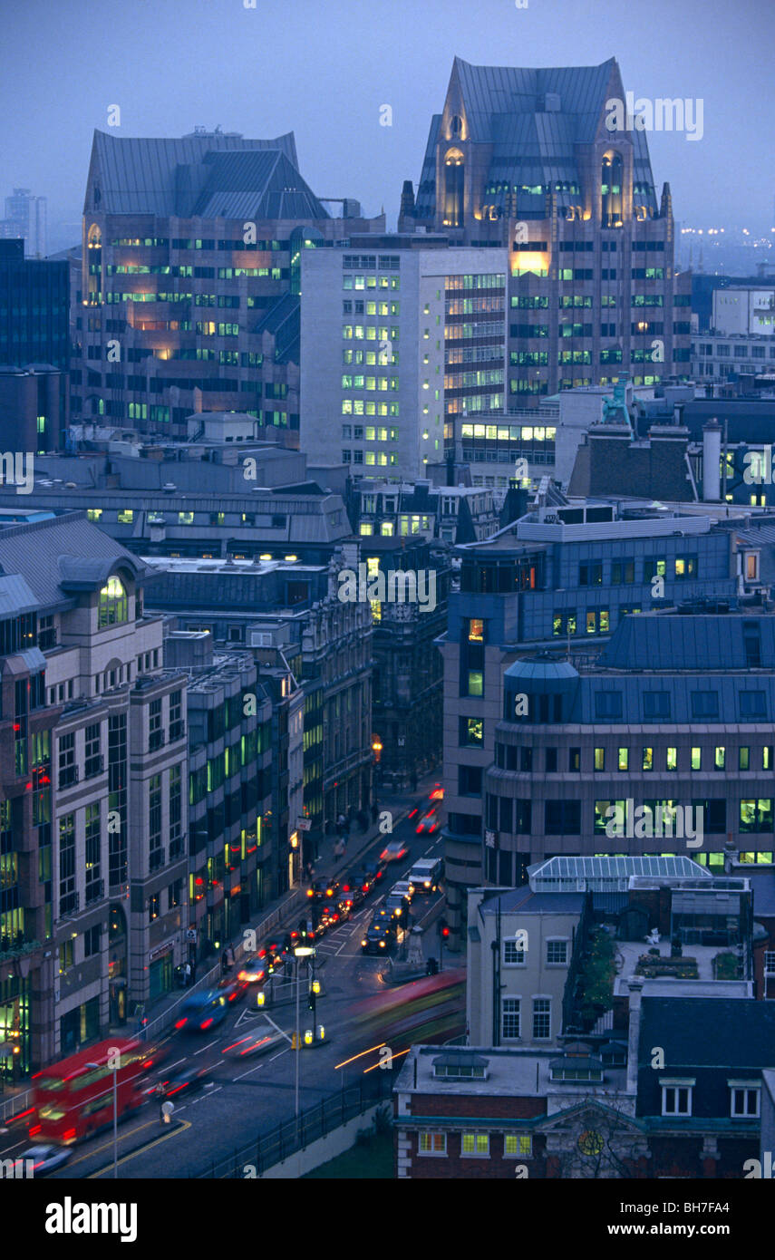 Lit offices and blurring traffic are seen at dusk from an aerial viewpoint overlooking a road junction at Aldgate - Stock Image