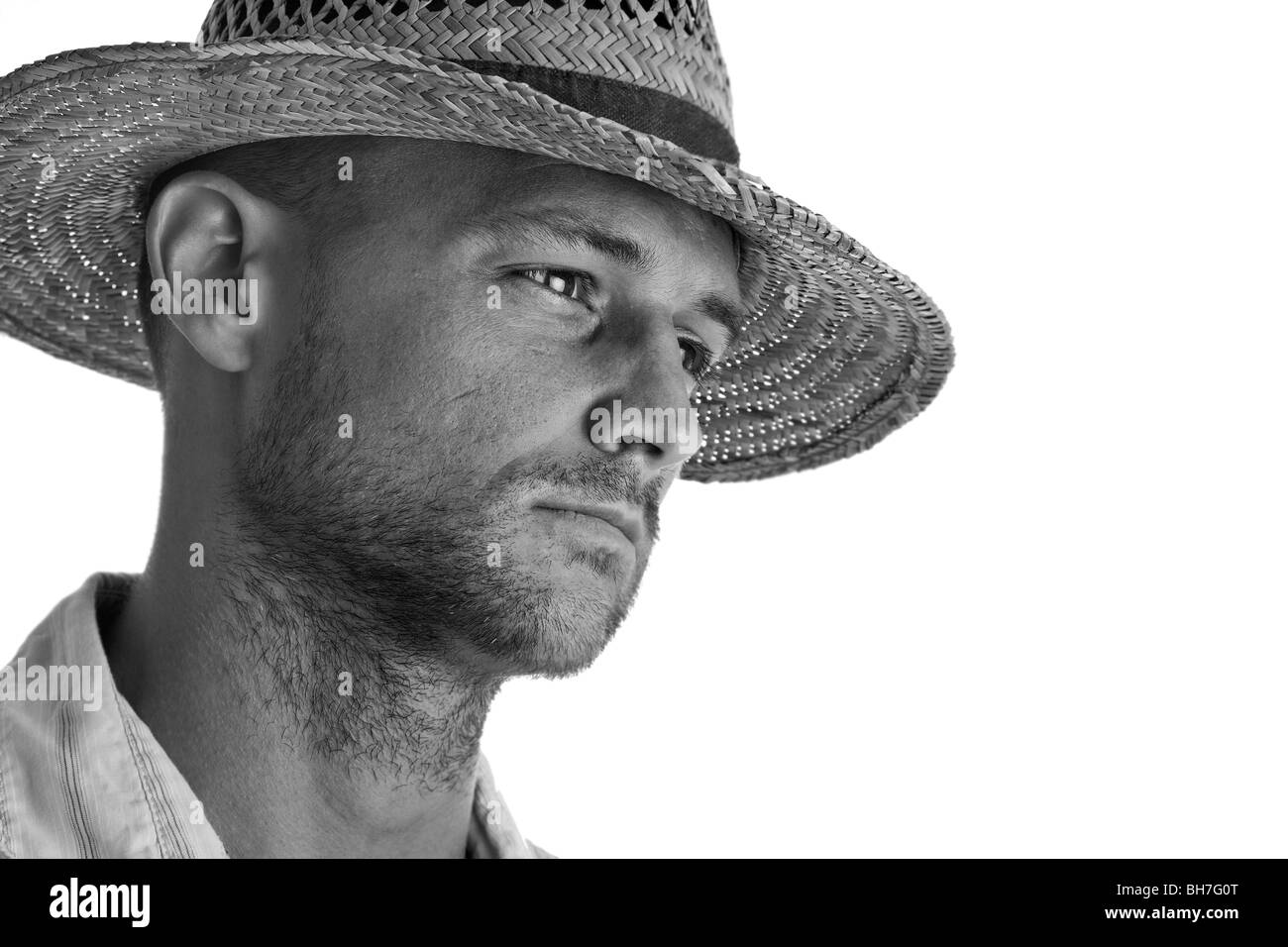 Portrait of a man in a straw hat, with a studio white background, in attractive mono - Stock Image