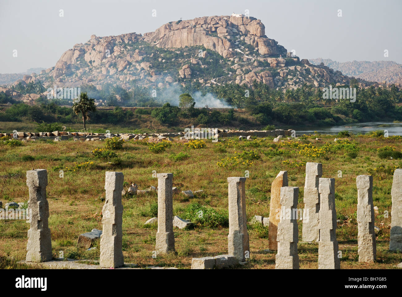 Ancient bridge in ruins with the river and a rocky hill in the background. Hampi,India. - Stock Image