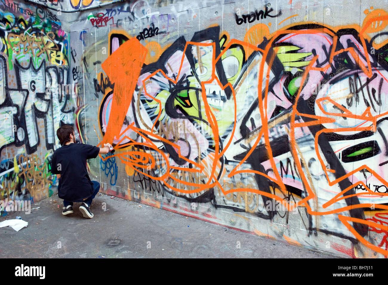 Spray painting graffiti on concrete wall south bank london england uk