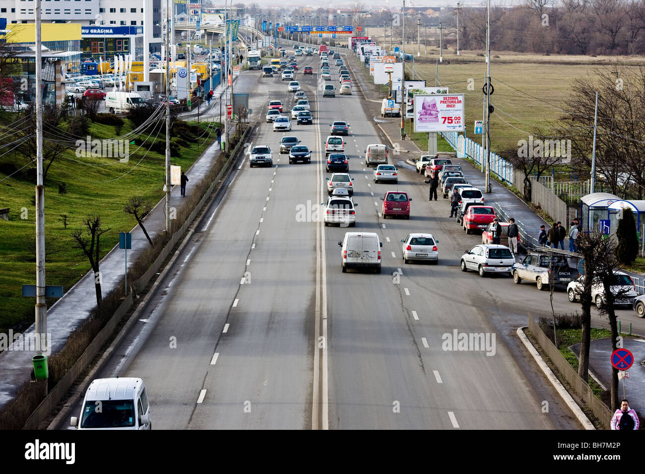Cars and pedestrians on the DN1 arterial road to Oradea on the outskirts of Cluj-Napoca Romania - Stock Image