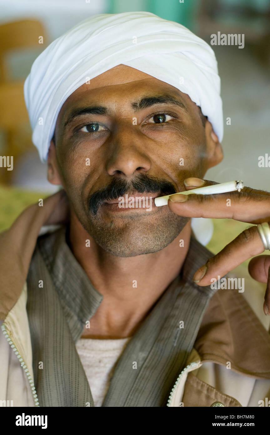 Portrait of an Arab Muslim Egyptian man wearing a headscarf and smoking a lit cigarette, in the Saharan town of - Stock Image