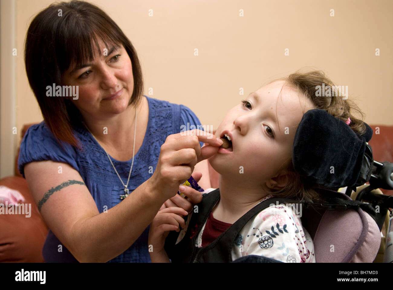 Working mother caring for her disabled daughter at home who suffers from cerebral palsy, Luton, UK. - Stock Image