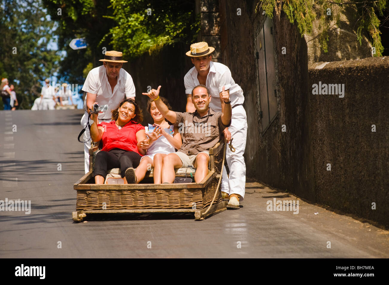 Tourists descend the steep streets of Monte in a traditional tobogan, Funchal, Madeira - Stock Image