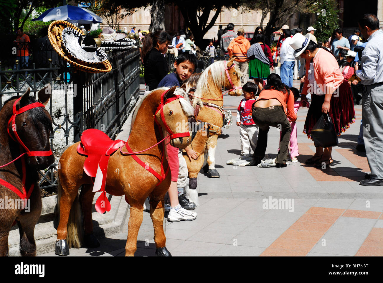 Ecuador, Cuenca, children riding small fake horses on the Park Abdon Calderon with some indigenous women wearing - Stock Image