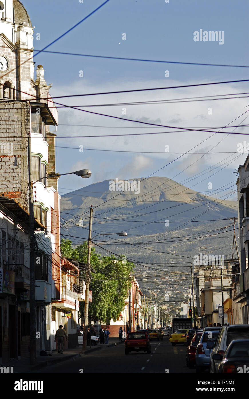 Ecuador, Ibarra, view of crowded urban scene in front of a volcano against cloudy sky - Stock Image
