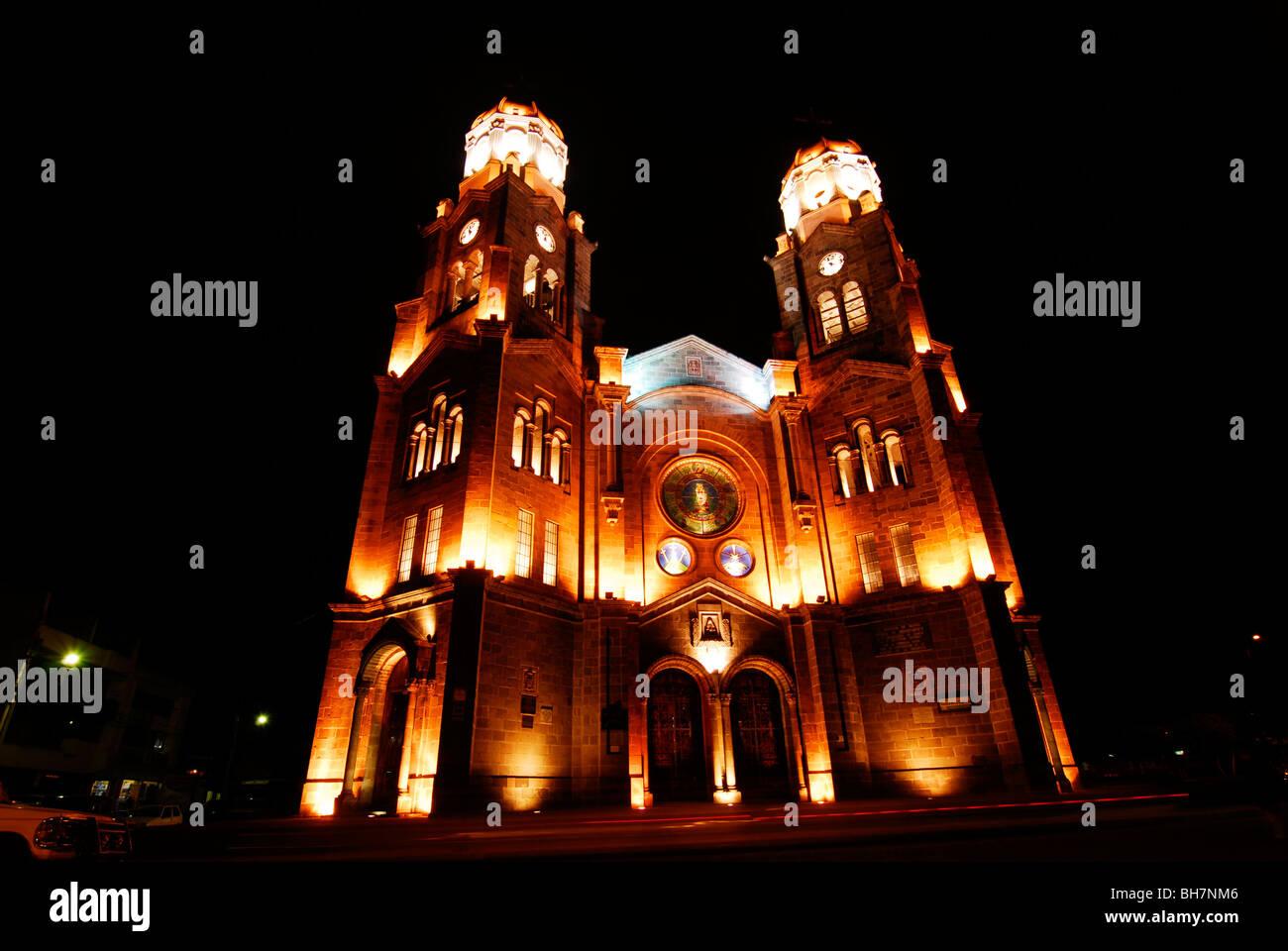 Ecuador, Ibarra, low angle view of the Ibarra brightly illuminated catholic church at night - Stock Image