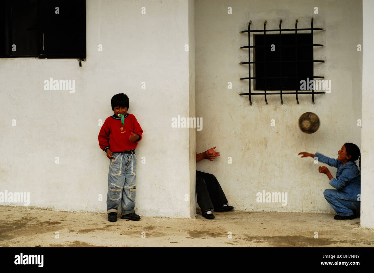 Ecuador, Latacunga, children playing with ball by a wall Stock Photo