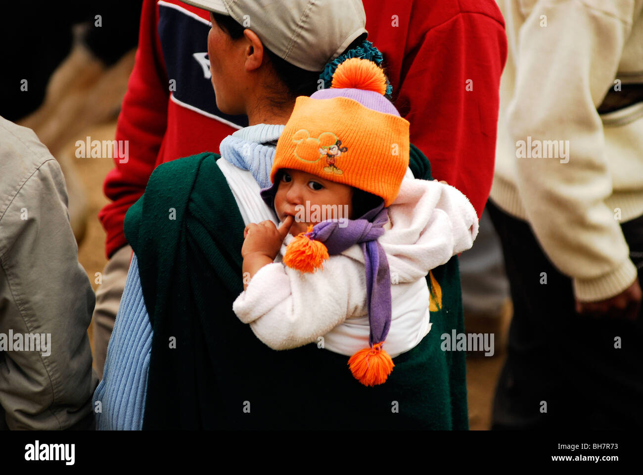 Ecuador, Otavalo, rear view of a baby wearing an orange wool cap his finger stuck in his mouth carried on the back Stock Photo