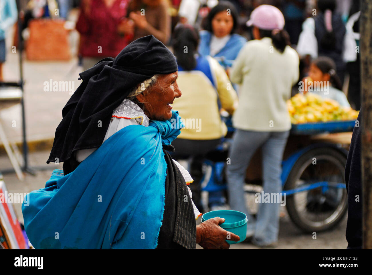Ecuador, Otavalo, rear view of a senior woman begging in the market holding a blue plastic pot, a blue fabric wrapped Stock Photo