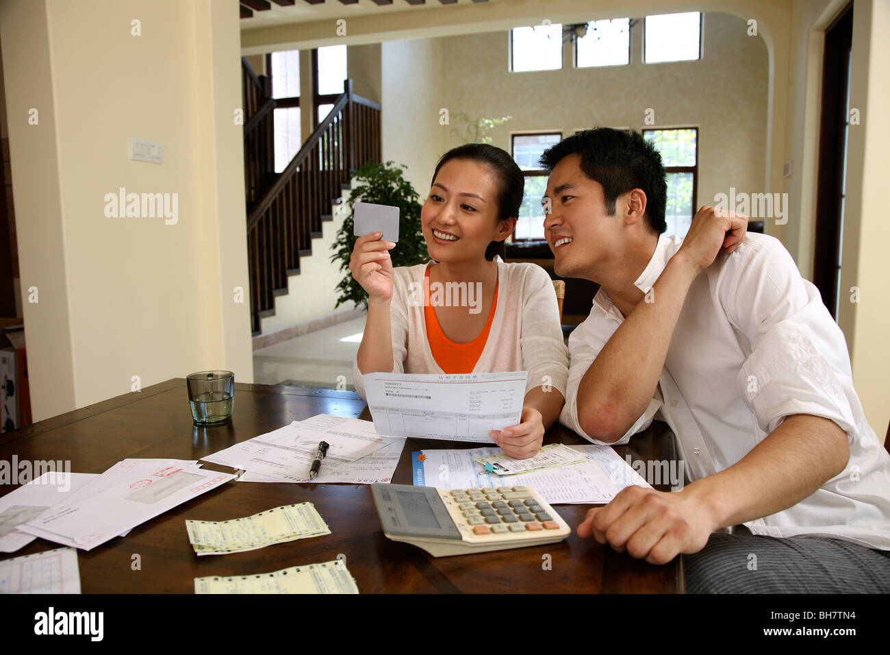 Chinese young coule sitting at table with bank statements - Stock Image