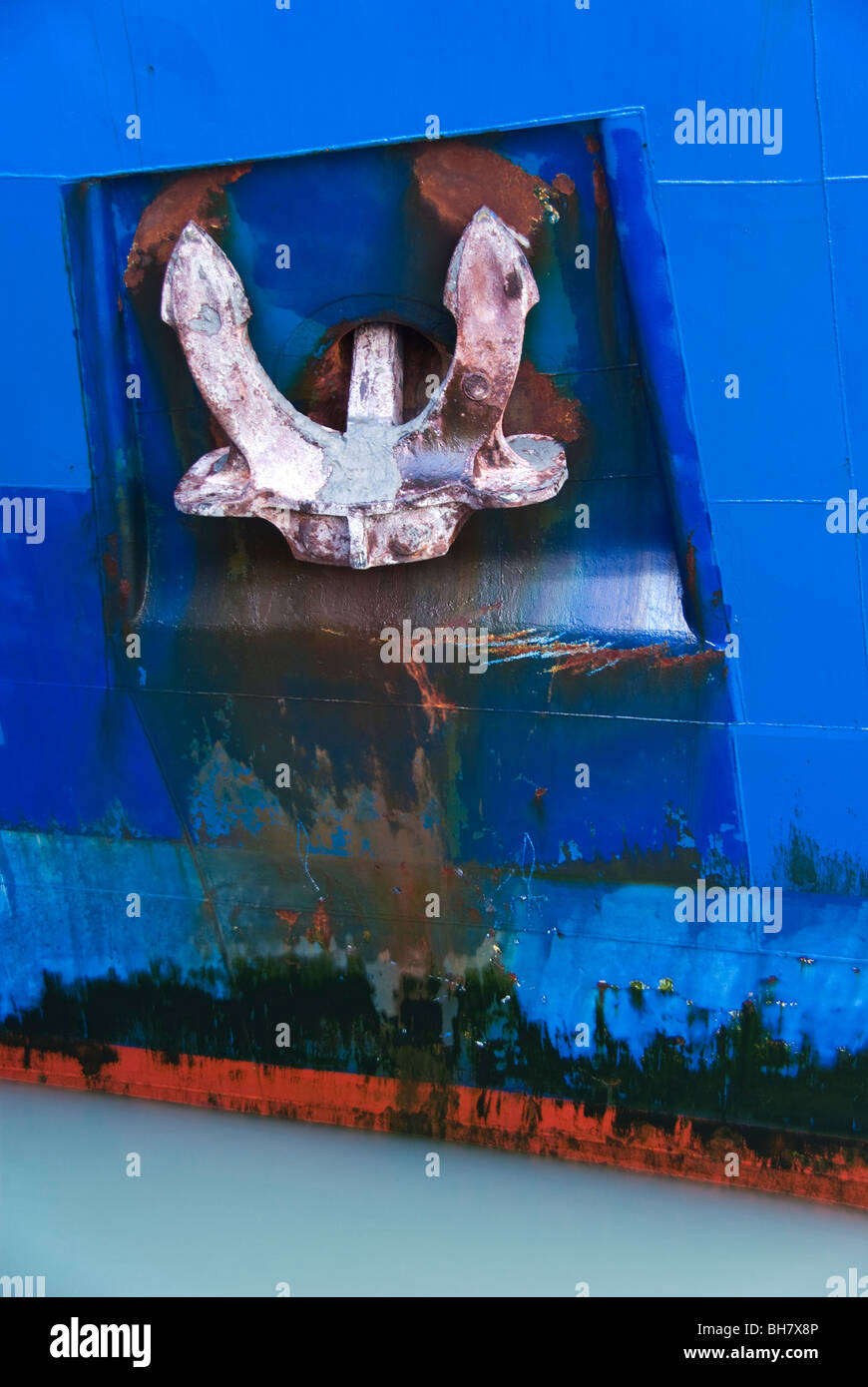 A close - up view of a ship's anchor housed in it's hawse pipe recessed in the hull. - Stock Image