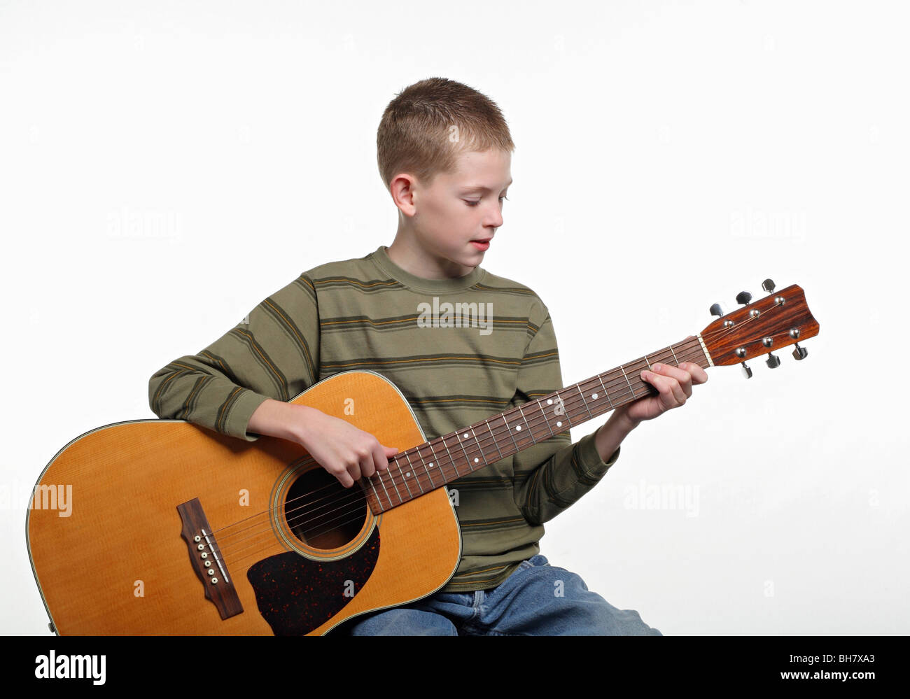 elementary age child sitting and playing a large acoustic guitar - Stock Image
