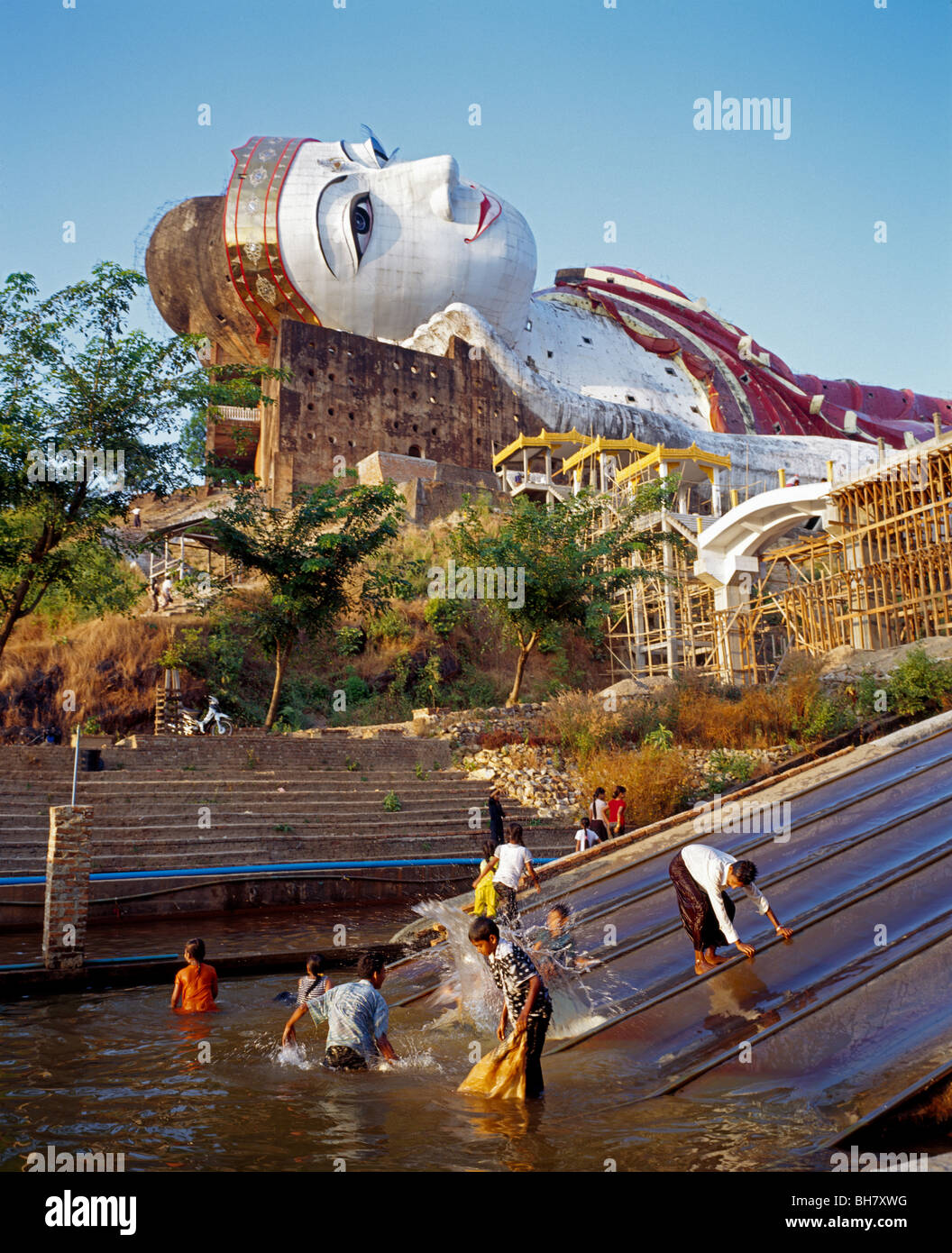 Children playing in the water of a playground slide at Giant Reclining Buddha at Win Sein Taw Ya Monastery Myanmar - Stock Image