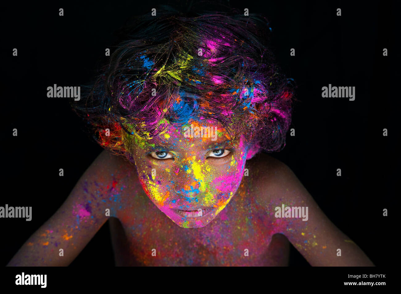 Young Indian boy covered in coloured powder pigment against a black background. India - Stock Image