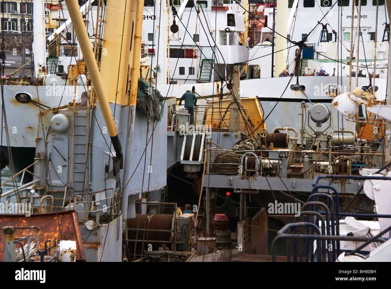 Trawlers moored against each other while not at work between fishing seasons . - Stock Image