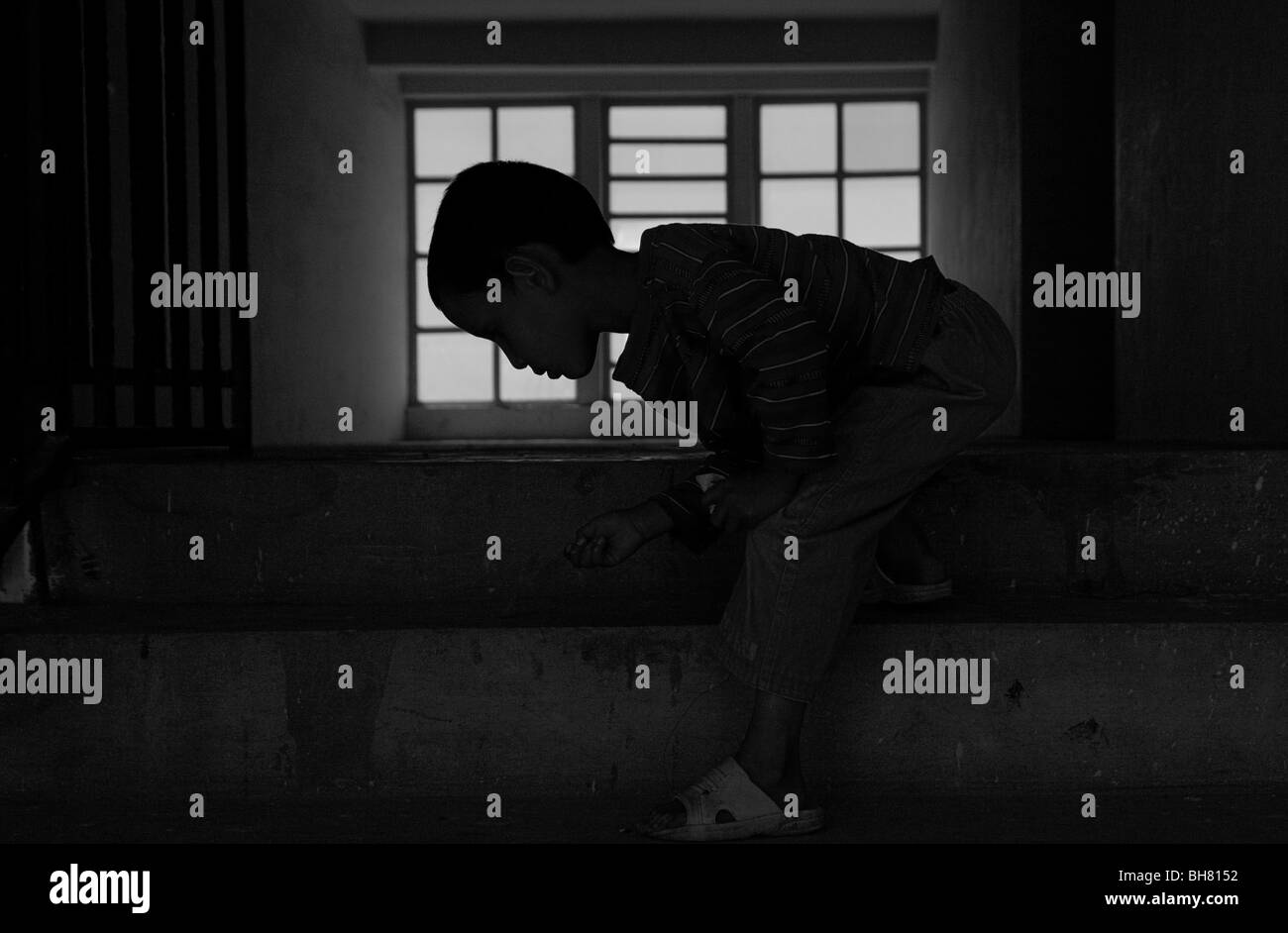 Child cleaning stairwell in social housing center in Kabul Afghanistan - Stock Image
